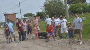 Sin asfalto y cansados del abandono, vecinos con palas arreglan su calle