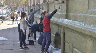 Archivo. Estudiantes universitarios pintando el frente de la Facultad de Ciencias Económicas.
