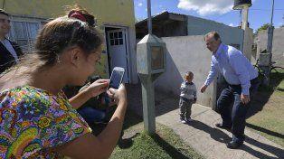 En san salvador. El gobernador con un gurisito que lo mira desconfiado, pero su mamá quiere tener la foto.