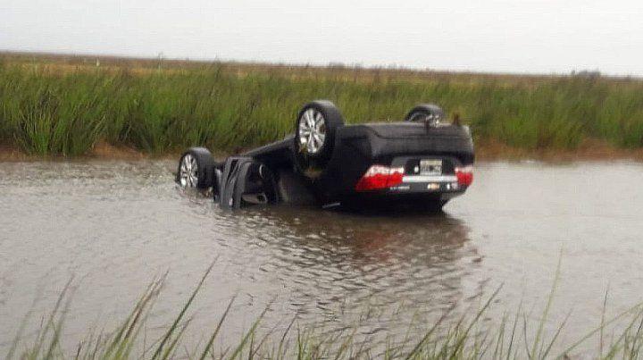 Volcaron bajo la lluvia y el auto quedó semisumergido