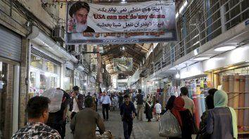 Vida diaria. En el gran bazar de Teherán, una pancarta del régimen arenga al público que sufre la carestía, agravada por las sanciones de EE.UU.