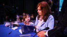 Cristina firma su libro con una pequeña seguidora que la mira embelesada.