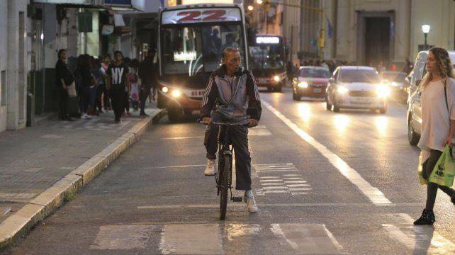 El ciclista espera que cruce la mujer mientras se vienen los autos y colectivos.