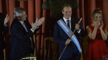 El presidente Fernández aplaude a Bordet con la banda y el bastón junto a su vice Laura Stratta.