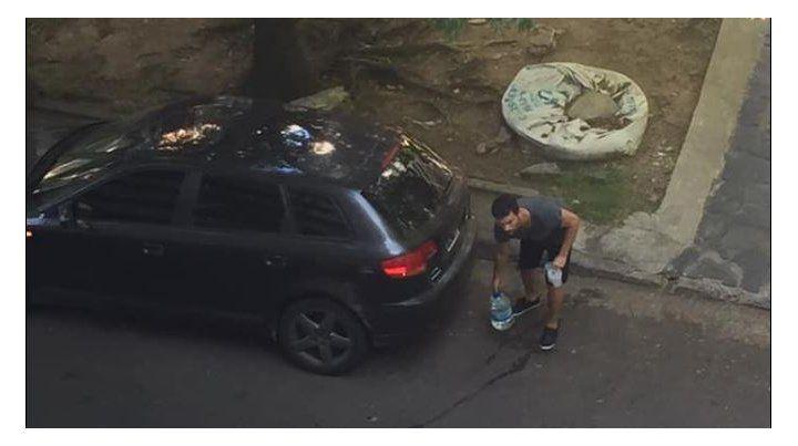 El muchacho bajando los bidones del auto.