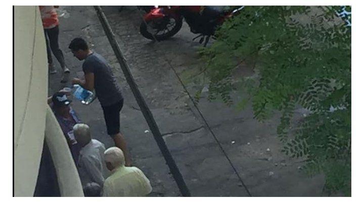 Pablo sirviendo agua en la fila del banco.