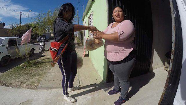 Chuni entregando el pan a una vecina.
