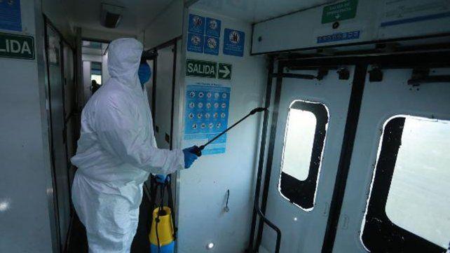 Un empleado higienizando uno de los vagones del tren que vuelve a unir Paraná con Colonia Avellaneda.